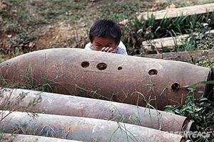 Niño en Laos jugando junto a una bomba de racimo.